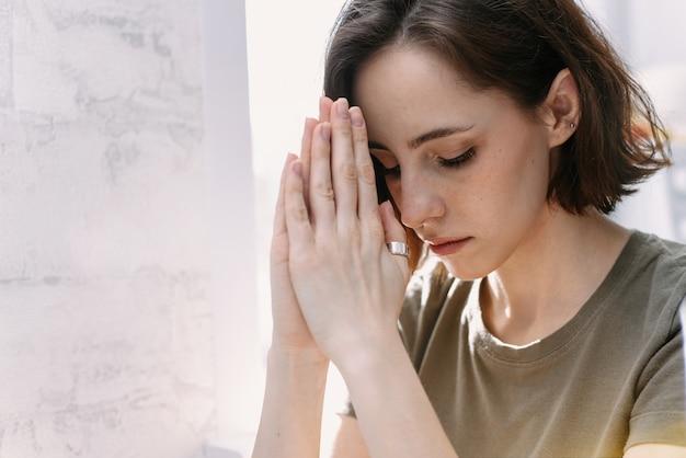 Linda linda garota cruzou as mãos em oração. uma mulher pede ajuda a deus.