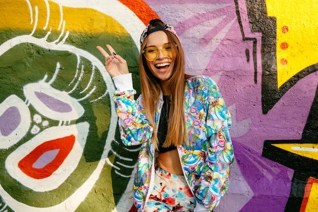 Linda linda garota de óculos, mostrando o gesto de paz, olhando para a câmera, amplamente sorrindo
