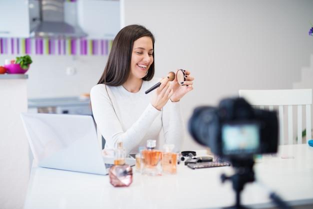 Linda linda garota jovem está sentado na mesa da cozinha com um laptop e mostrando perfumes e cosméticos para a câmera enquanto rindo.