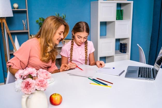 Linda linda garota na escola primária fazendo os deveres de casa em casa
