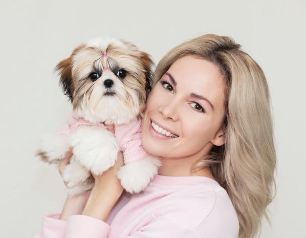 Linda linda garota segurando um filhote de shih tzu bem preparado em um suéter rosa