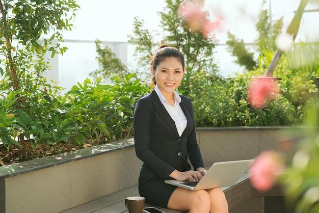 Linda linda garota sorrindo com roupas de mulher de negócios, usando o laptop no parque