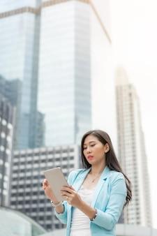 Linda linda garota vestindo roupas de mulher de negócios, segurando um computador tablet de telefone inteligente no fundo da cidade urbana de distrito comercial, conceito de negócio