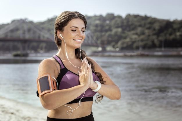 Linda localização. mulher alegre e feliz juntando as mãos enquanto medita na praia
