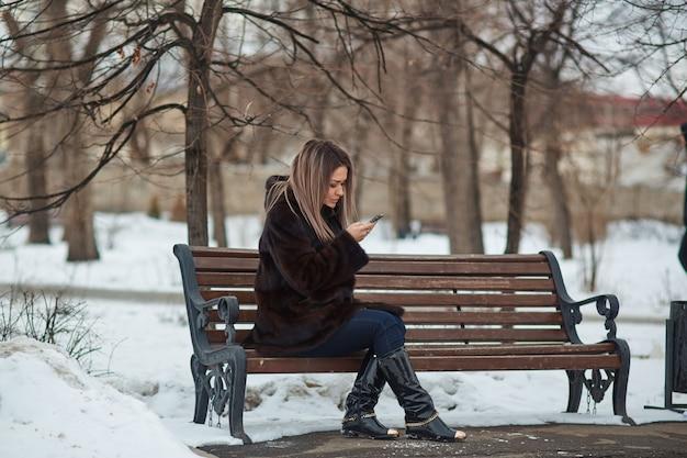 Linda loira aparência caucasiana com um casaco de pele, sentado em um parque em um banco no inverno e falando ao telefone