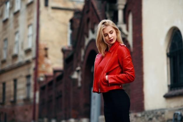 Linda loira atraente com figura perfeita em uma jaqueta de couro vermelha e saia preta justa