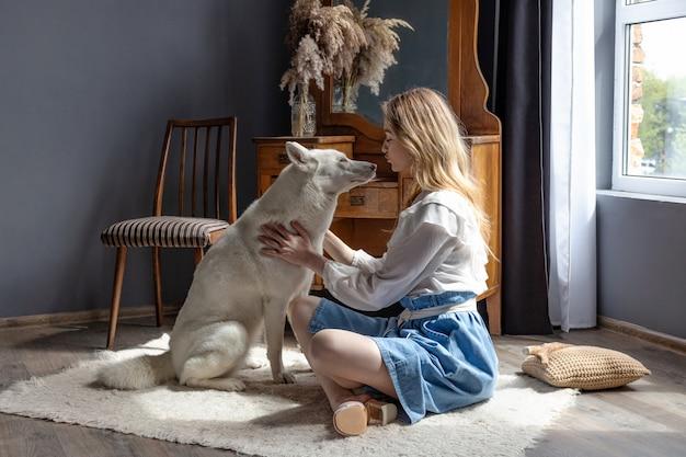 Linda loira brincando com cachorro husky branco