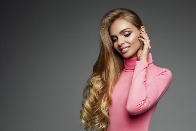 Linda loira cabelos compridos com pele perfeita e maquiagem no pescoço de tartaruga rosa sobre cinza.