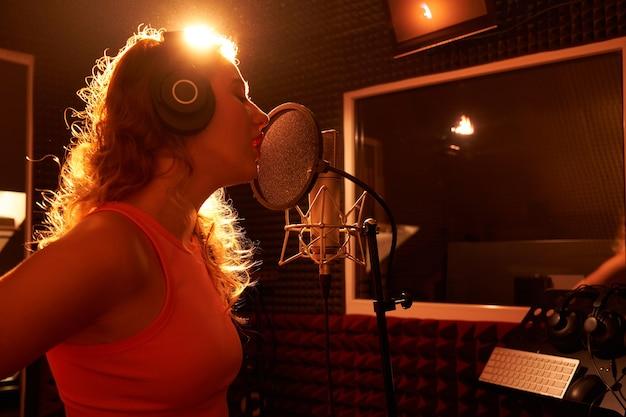 Linda loira cantando uma música no estúdio de gravação com microfone e fones de ouvido profissionais