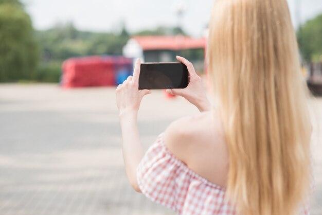 Linda loira caucasiana segurando um smartphone nas mãos e tirando foto