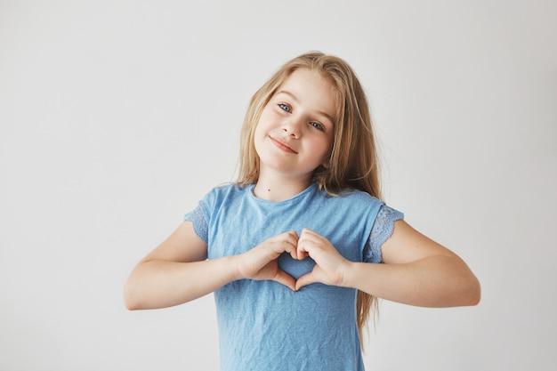 Linda loira com cabelos claros na camiseta azul com sorriso gentil, fazendo gesto de coração com as mãos, posando para o ensaio fotográfico de escola.