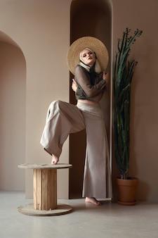 Linda loira com chapéu de palha, blusa e calça larga, posando perto de planta suculenta