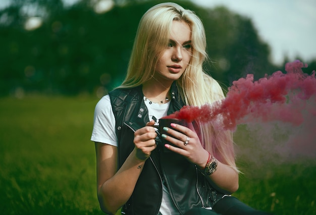 Linda loira com copo com fumaça vermelha