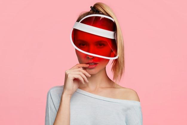 Linda loira com rabo de cavalo e um chapéu vermelho da moda