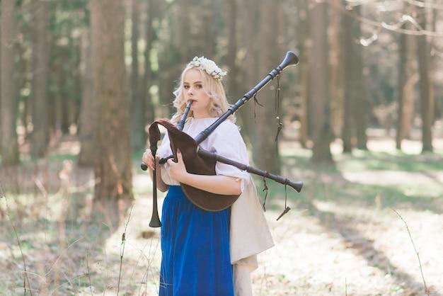 Linda loira com roupas eslavas tocando flauta e cachimbo na floresta de verão