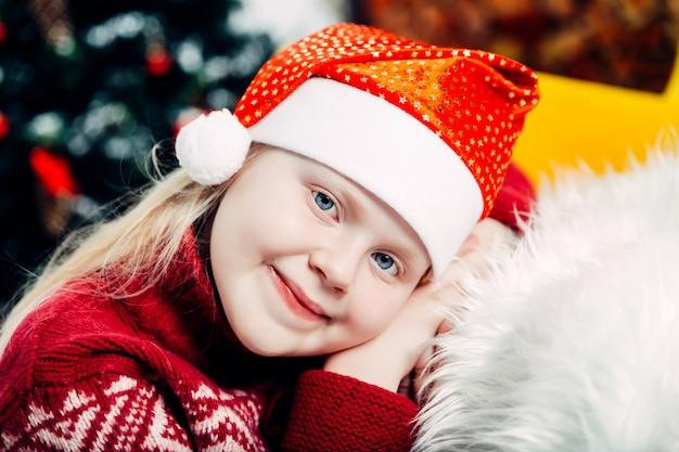 Linda loira com um chapéu de natal sonhadora olhando para longe no interior do ano novo