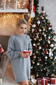 Linda loira com um suéter aconchegante mantém um copo de bebida quente e posando perto da árvore de natal no interior decorado para o ano novo