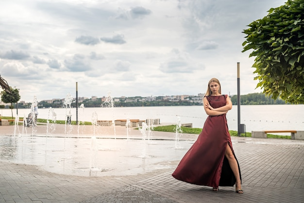 Linda loira com um vestido longo vermelho escuro posando na lagoa, romântica
