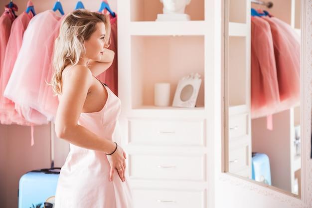 Linda loira com uma camisa rosa se olha no espelho em seu camarim ou quarto.