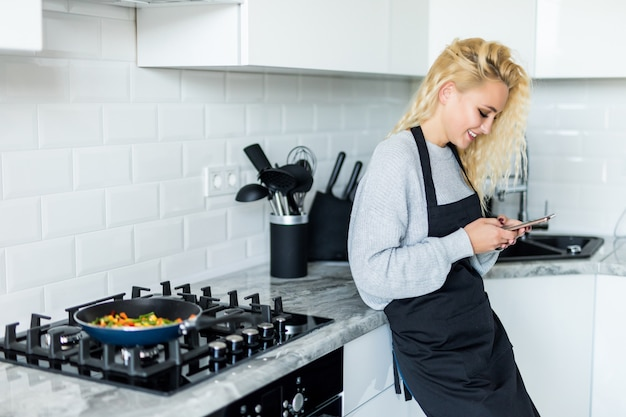 Linda loira cozinhar comida na frigideira, use no telefone celular e sorrindo enquanto cozinhava na cozinha em casa