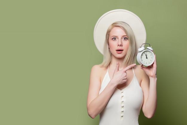 Linda loira de chapéu branco e vestido com despertador