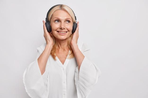 Linda loira de cinquenta anos ouve música em fones de ouvido sem fio ouve uma música relaxante, sorrisos e usa blusa em poses contra a parede branca