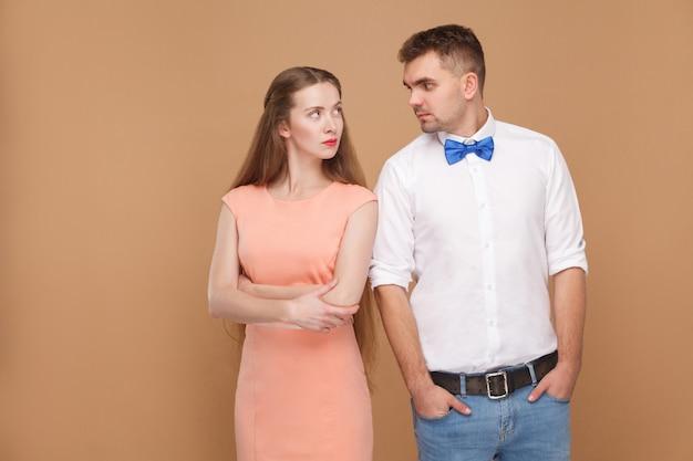 Linda loira de vestido rosa olhando uma para a outra com uma cara séria