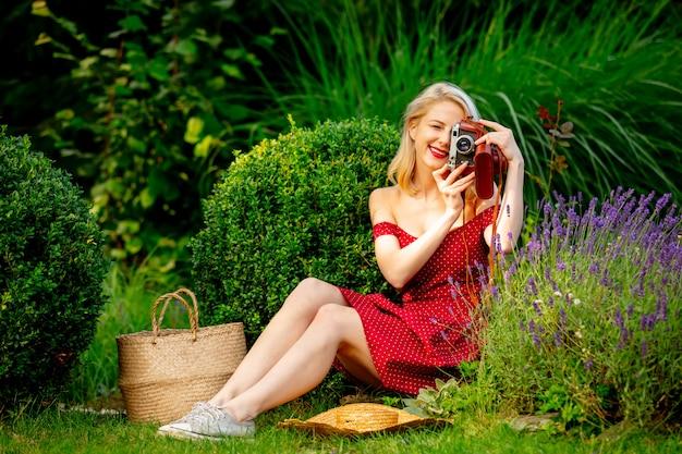 Linda loira de vestido vermelho com câmera vintage em um jardim