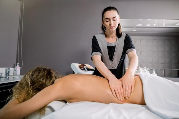 Linda loira deitada no sofá no centro de spa moderno, enquanto o massagista jovem está massageando ela de volta.