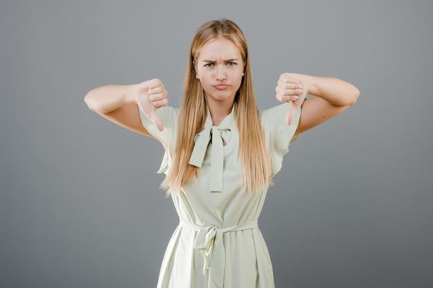 Linda loira desapontada, mostrando os polegares para baixo isolado
