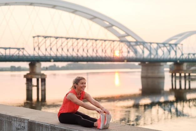 Linda loira desportiva esticando os músculos à beira do rio e aproveitando a manhã tranquila de verão.