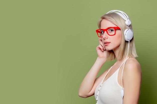 Linda loira em copos com fones de ouvido