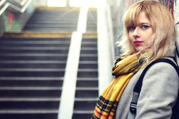 Linda loira em pé perto de uma parede com grafite em uma passagem subterrânea