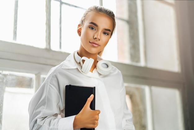Linda loira em uma camisa branca com fones de ouvido segurando um caderno preto.