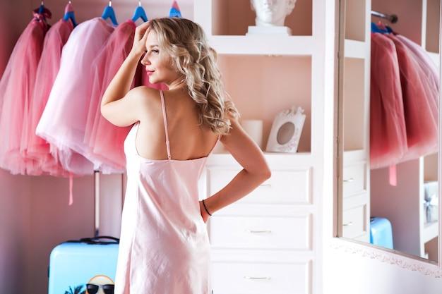 Linda loira em uma camisa rosa pozirket em seu camarim ou quarto. a menina fica de costas para o espelho