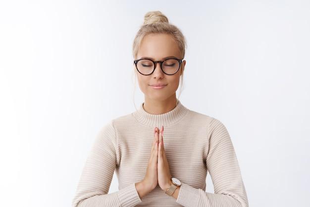 Linda loira empresária de óculos relaxando olhos fechados e sorrindo aliviada e relaxada meditando segurando as palmas das mãos juntas em namastê ou gesto de oração, praticando ioga sobre uma parede branca