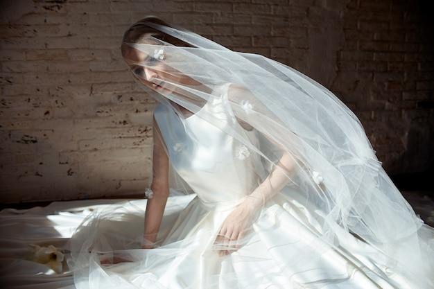 Linda loira esbelta, sentada no chão com vestido longo branco. retrato