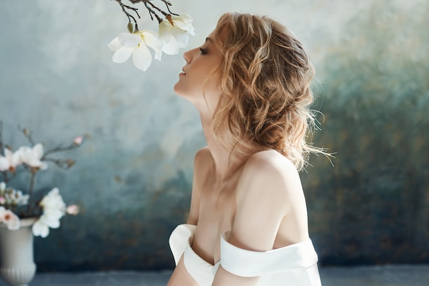 Linda loira esbelta, sentada no chão com vestido longo branco.