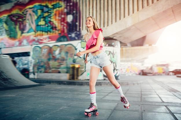 Linda loira está andando em rolos na sala de skate. ela está muito ativa. a menina usa short e blusa rosa. ela está feliz.
