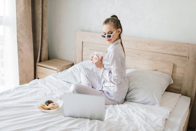 Linda loira estudando e trabalhando em uma cama com seu laptop