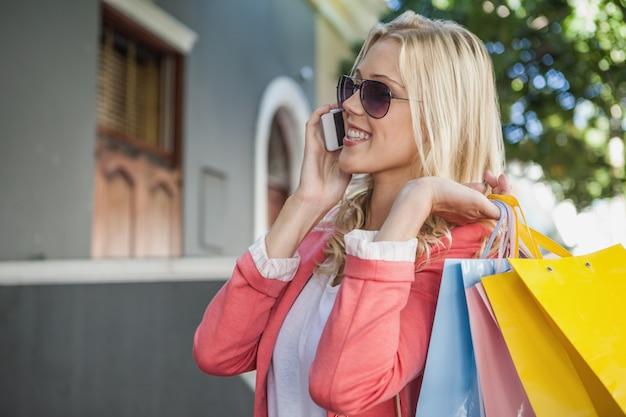 Linda loira falando no telefone segurando sacolas de compras