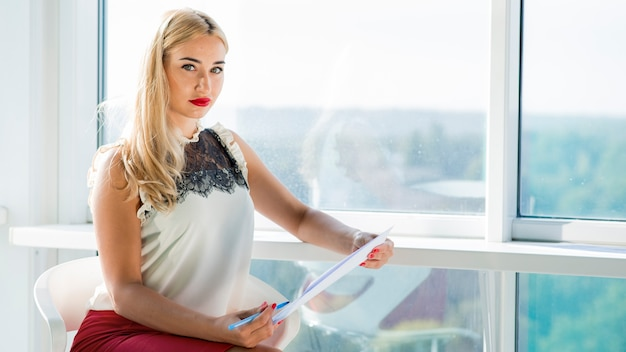 Linda loira jovem empresária sentado perto da janela, segurando o documento