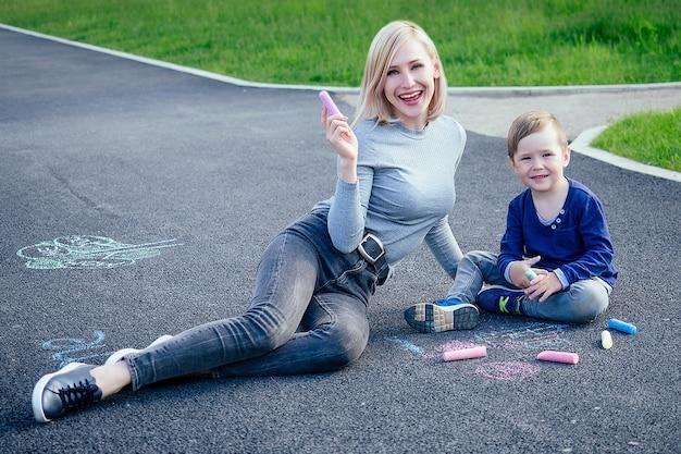 Linda loira mãe e seu filho lindo pintaram com giz de cera colorido no asfalto do parque em um fundo de grama verde.