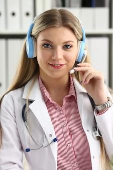 Linda loira médica falando com o paciente por meio de fone de ouvido sem fio