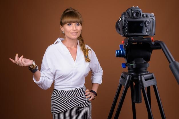 Linda loira mulher de negócios com cabelo trançado fazendo vlogs usando a câmera