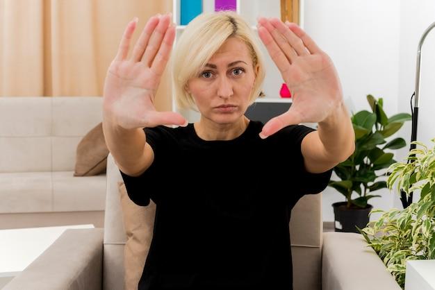 Linda loira mulher russa confiante sentada na poltrona, esticando as mãos olhando para a câmera dentro da sala de estar