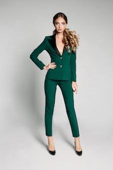 Linda loira no escritório verde terno e salto alto.