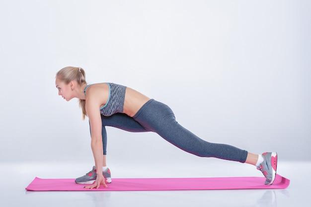 Linda loira no sportswear faz exercícios em um tapete de aptidão em um fundo cinza. alongamento