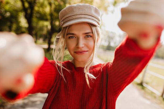 Linda loira num belo chapéu moderno e pulôver vermelho, fazendo selfie no parque outono.