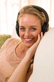 Linda loira, ouvindo música com fones de ouvido sentado no sofá